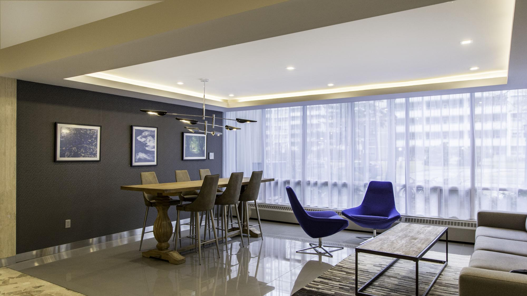 Lobby at an apartment building with blue chairs and a wooden table with high chairs surrounding it