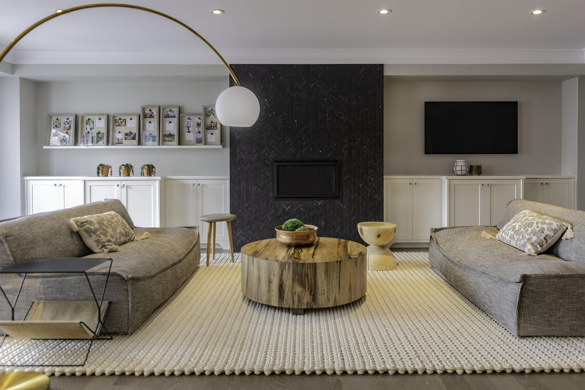 Great room with white carpet, grey couches, a black marble fireplace
