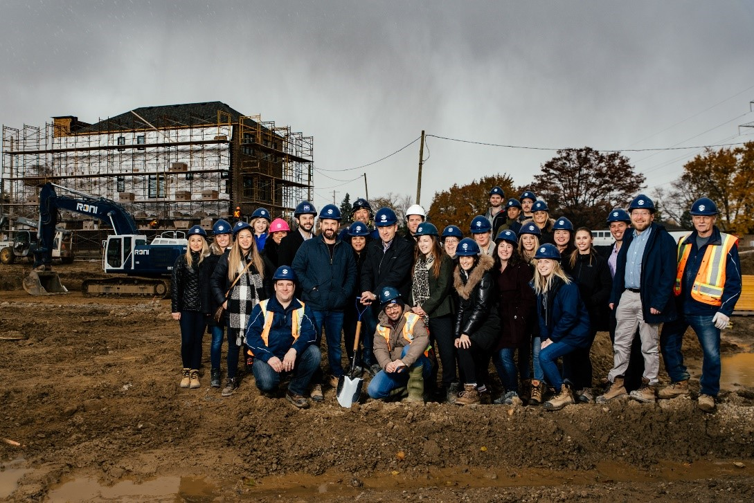 A group of Minto Group Employees standing in front of a model home with navy blue hard hats on