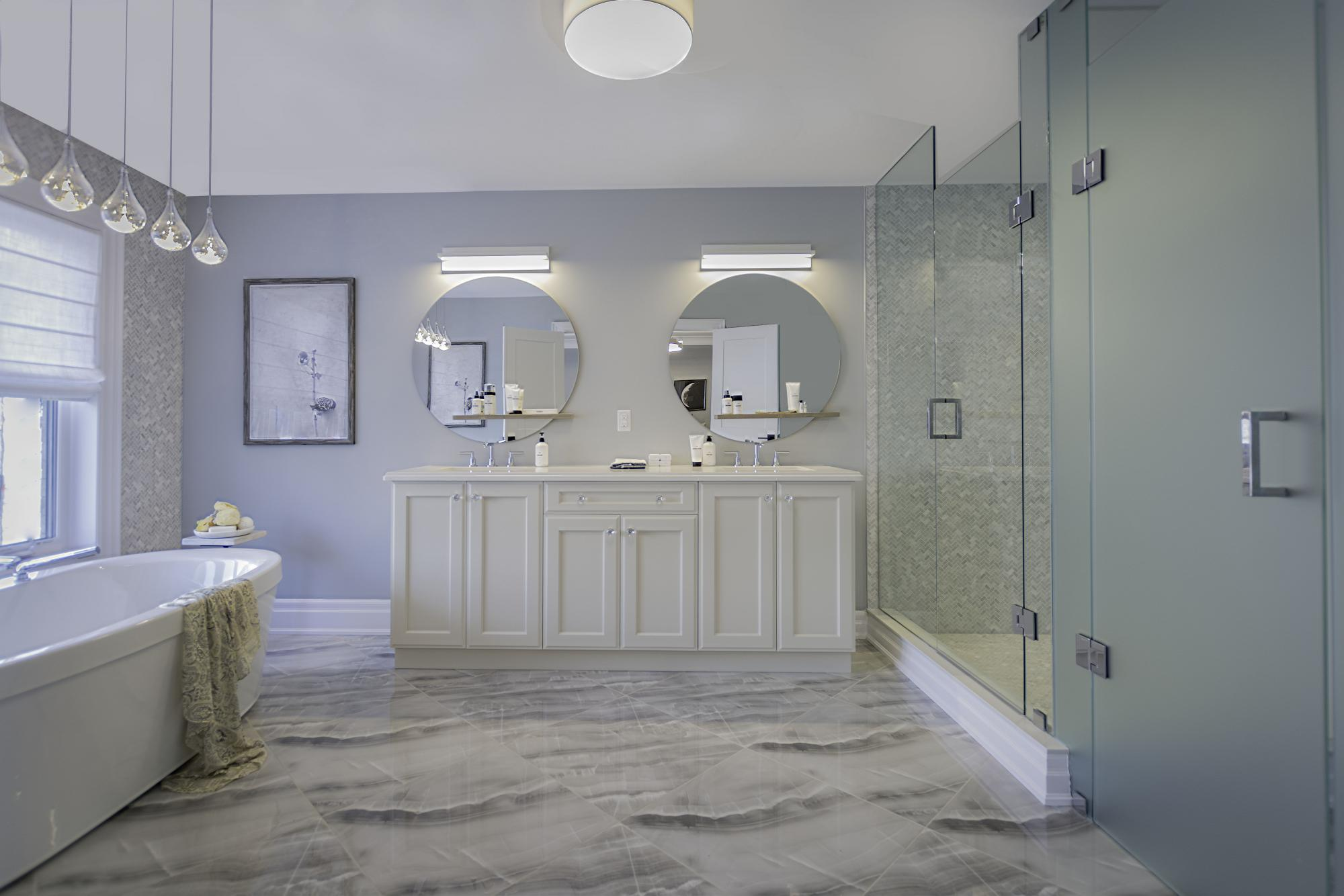Beautiful white bathroom with white marble floors, a deep soaker tub and a large shower. Two mirrors with two sinks