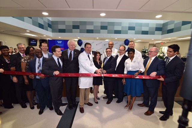 Doctors and business representatives posing with scissors at a ribbon cutting ceremony