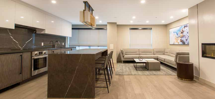 party room in an apartment with a big sectional sofa and kitchen