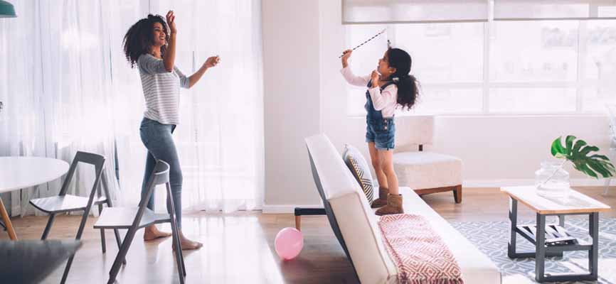 mom and daughter playing with pink balloons in the living room