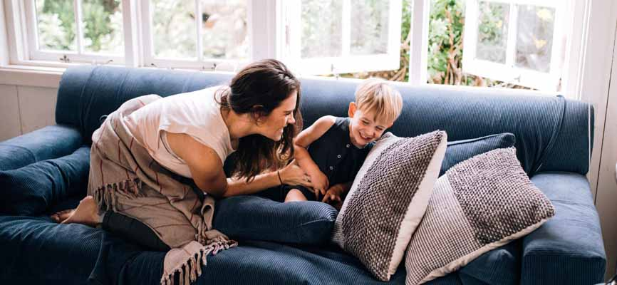 mom and son laughing on a couch with blankets and pillows