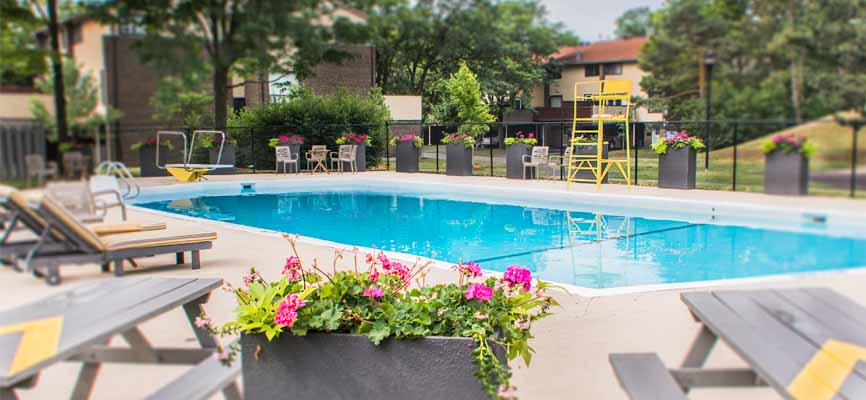 pool outside with grey picnic tables and flowers