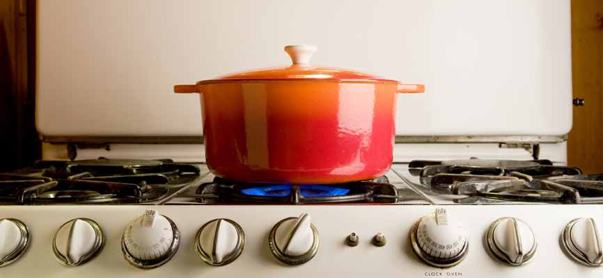 orange pot with lid on gas stovetop
