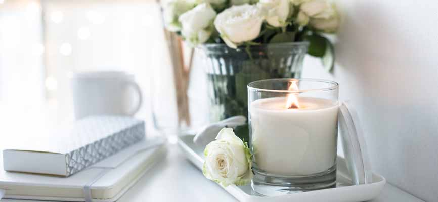 a candle, journal and bouquet of white roses on a table