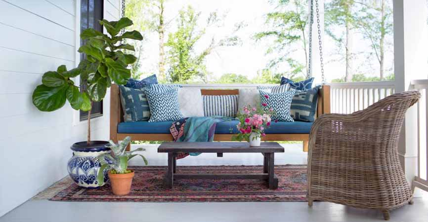 porch with plants and a hanging bench chair