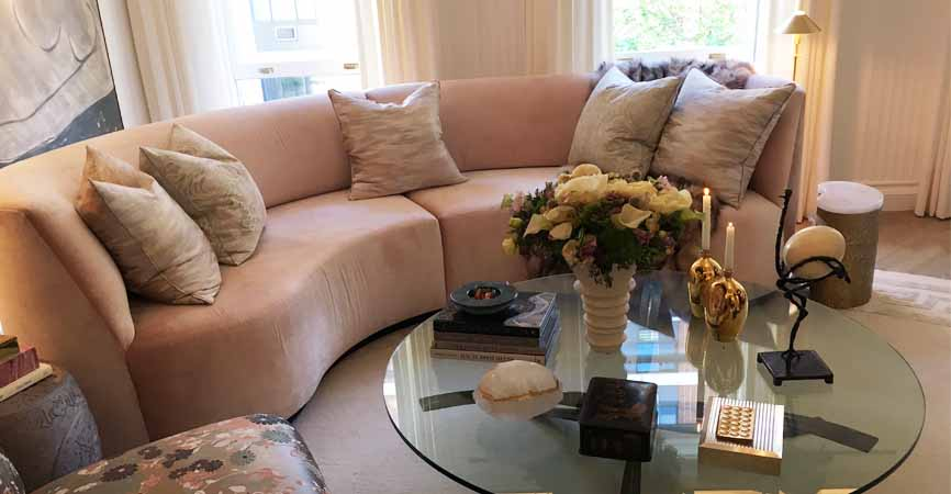 home with a pink curved couch and round coffee table