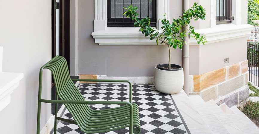 porch with plant, chair and checkered floors