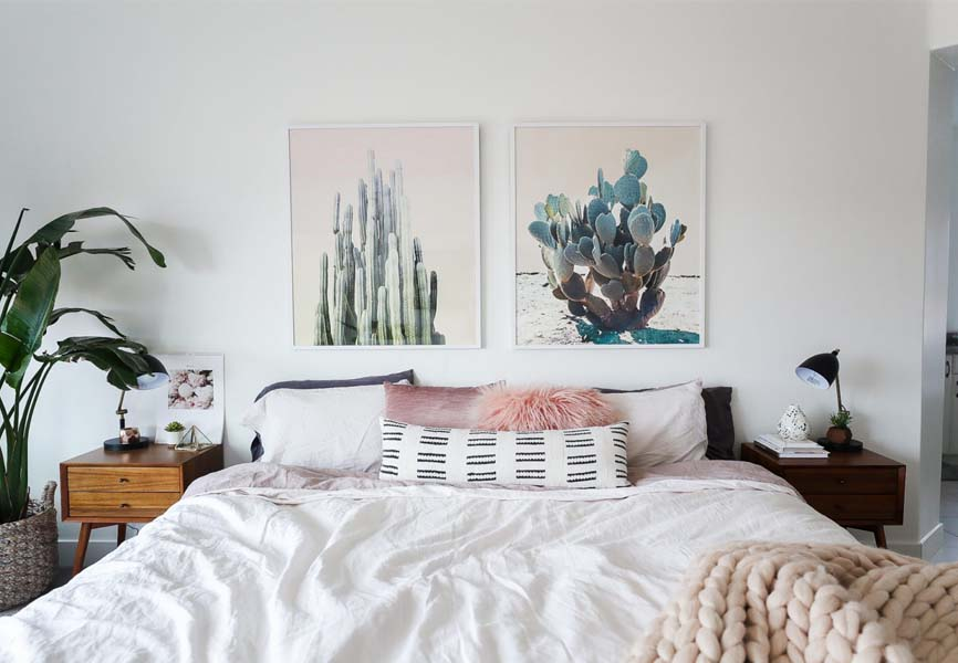 Bed with white covers, pink pillow, cactus paintings