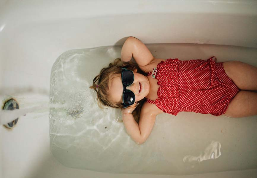 Little girl laying in a bathtub with sunglasses on her face