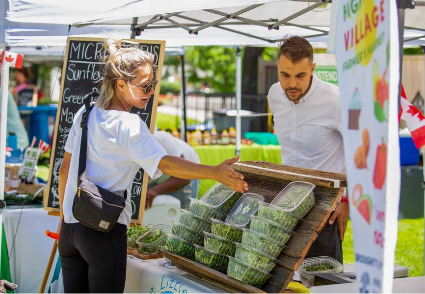 a man selling fresh greens to a woman at a farmers' market