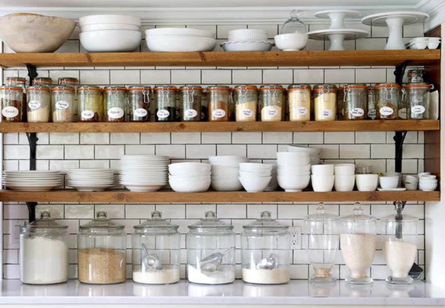 Spices, cups, bowls, and plates neatly organized on an open shelf