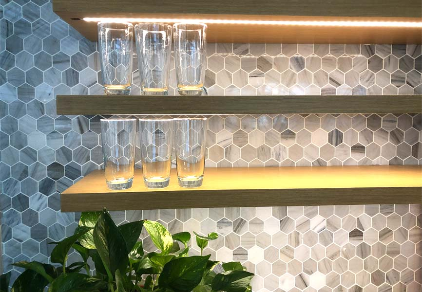 Water glasses on a shelf with a plant underneath and LED lights shining on top of them