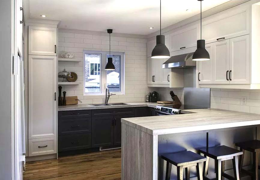 Laminate grey countertop and white cabinets with black ceiling lights