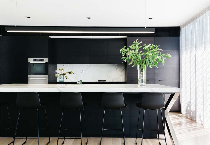 Kitchen with white marble countertop and black cabinets with black high chairs surrounding an island
