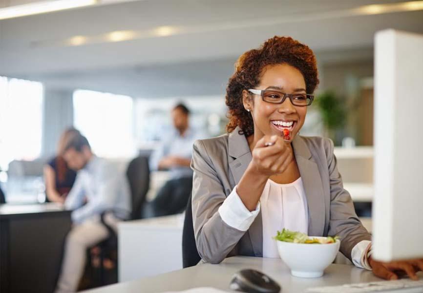 Girl eating a salad at her desk