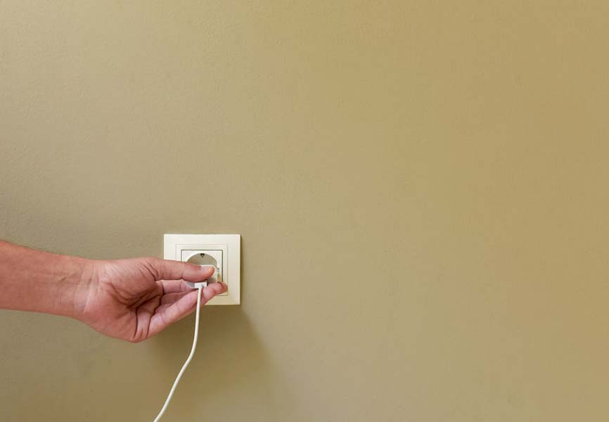 Hand plugging a cord into the wall