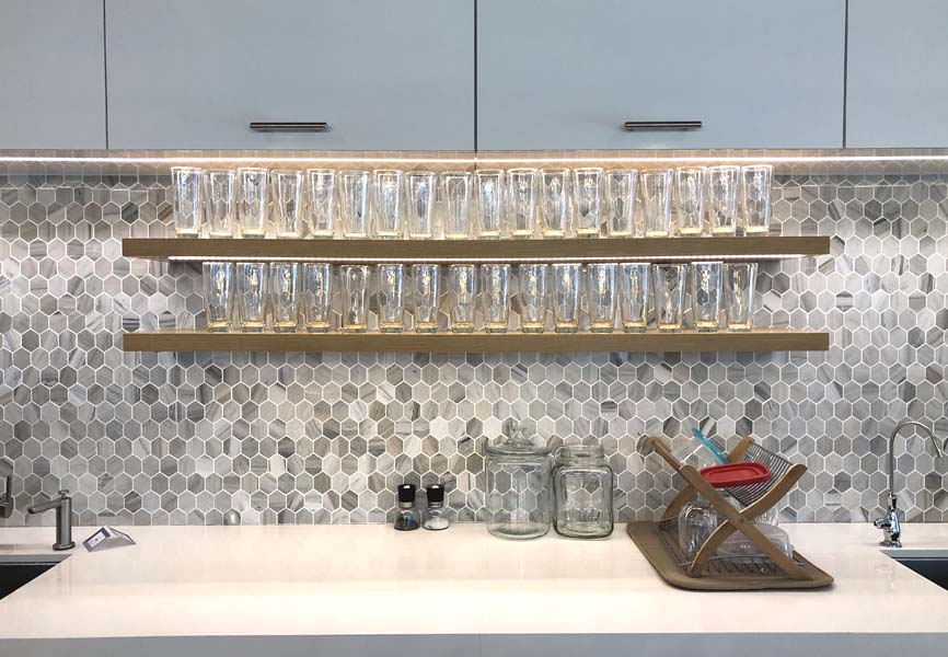 Water glasses sitting on top of a shelf