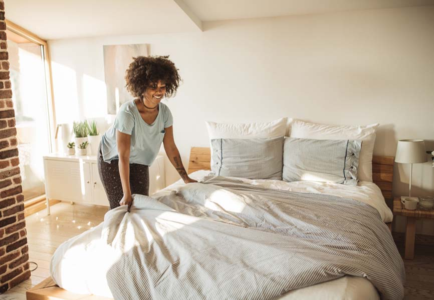 young woman smiling and making bed in the morning