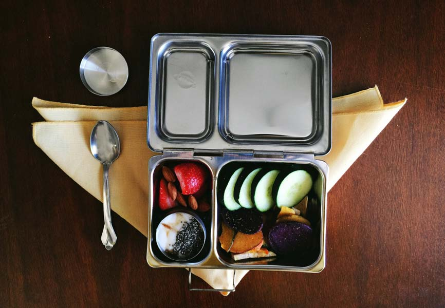 A tin lunch box with food inside