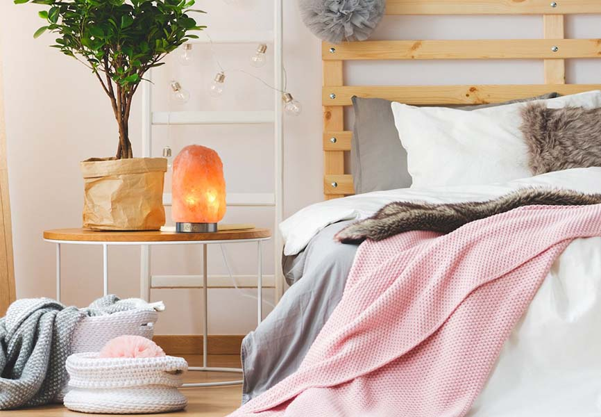 cozy pink bed with Himalayan salt lamp on bedside table