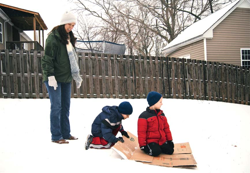 Two little boys using a cardboard box to sled while their mom watches them