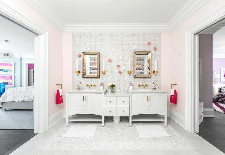 Little girls bathroom with two sinks, a pink wall, two mirrors with gold framing and white sink