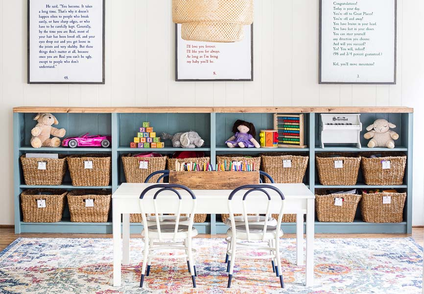 Childrens table in a playroom, in front of an organized toy shelf
