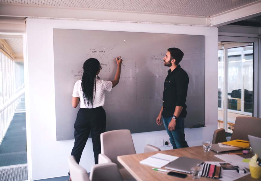 Two people writing on a white board