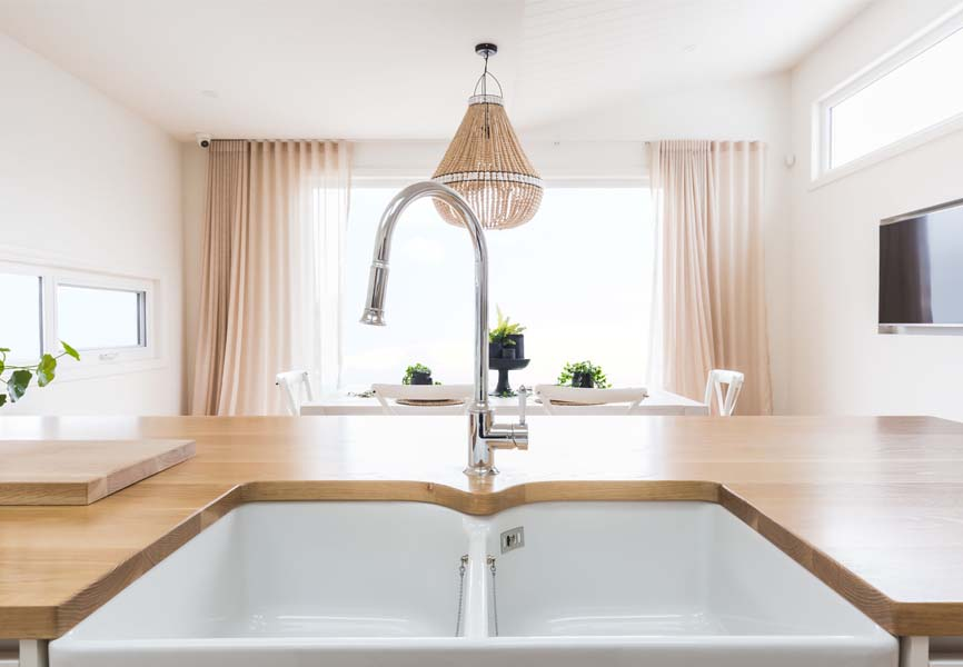 Wooden countertop with a white sunken sink and a chandelier in the background