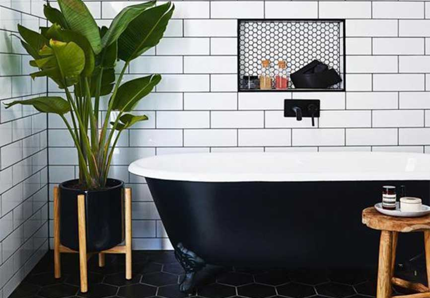 Tiled bathroom with a bathtub, plant, stool and mat