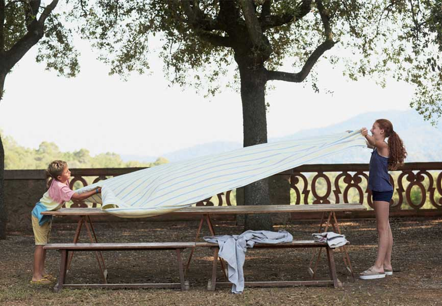 Young girl and boy putting a sheet over a bench