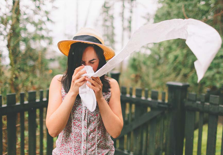 Woman blowing her nose into a long tissue