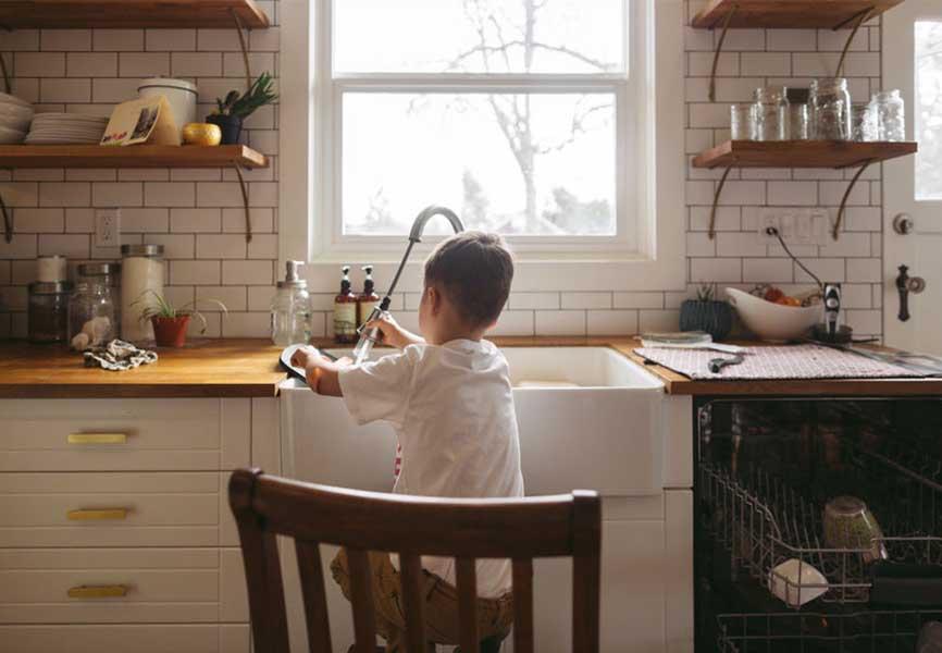Young boy washing dishes