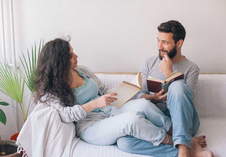 Couple on a couch with open books, dreamily staring into each other's eyes
