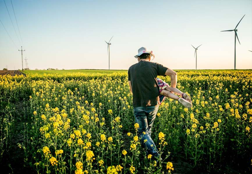 man carrying child through fields of flowers