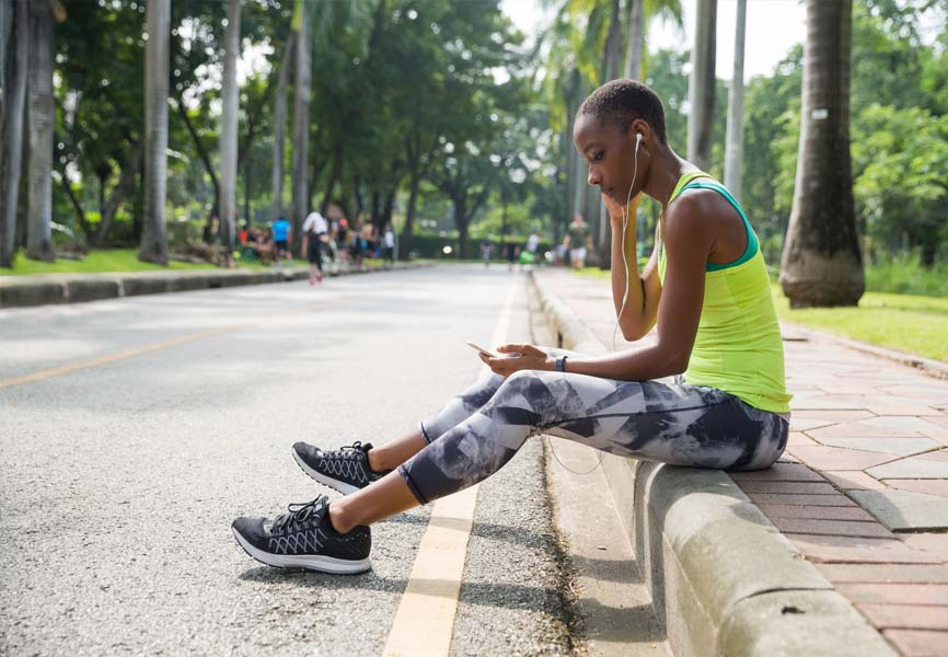 girl sitting on sidewalk in fitness clothes looking at phone with headphones in