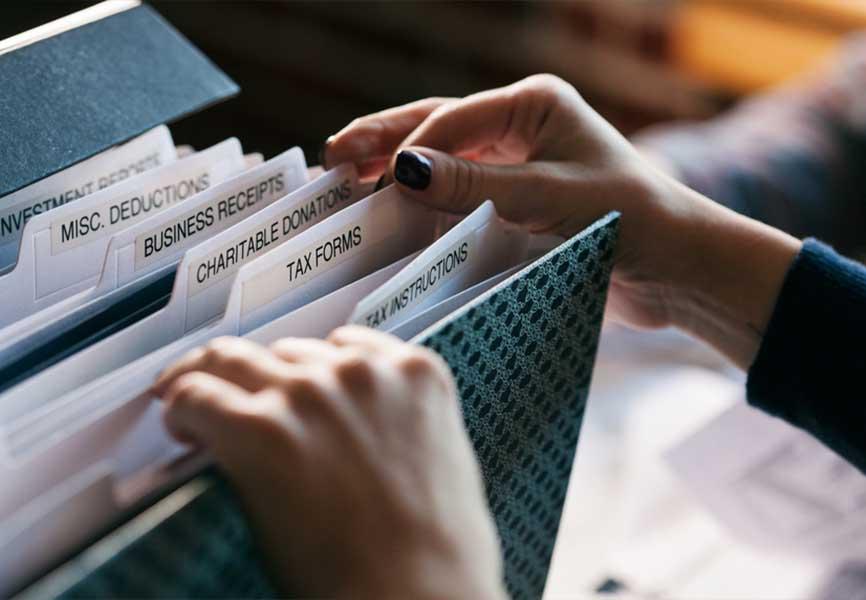 Hand sorting through file folders