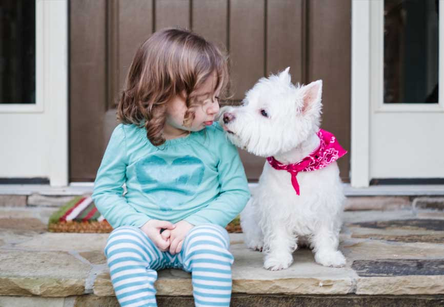 Little girl sitting next to a small white dog