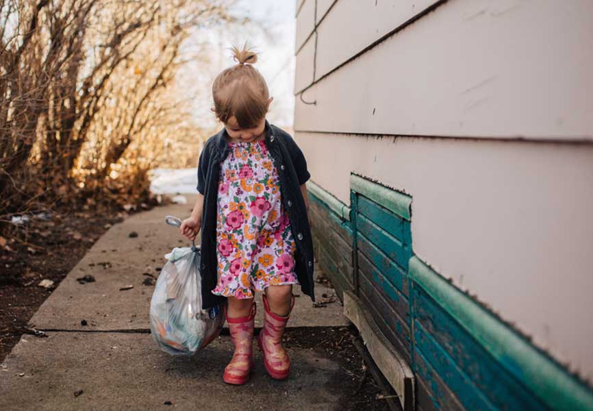 Little girl holding a bag of garbage
