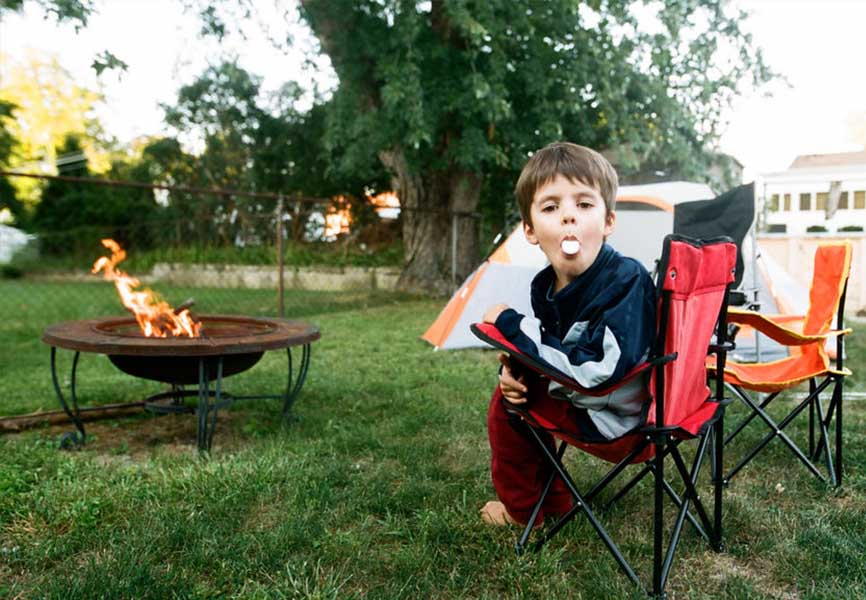 Boy at a campfire with a marshmallow in his mouth