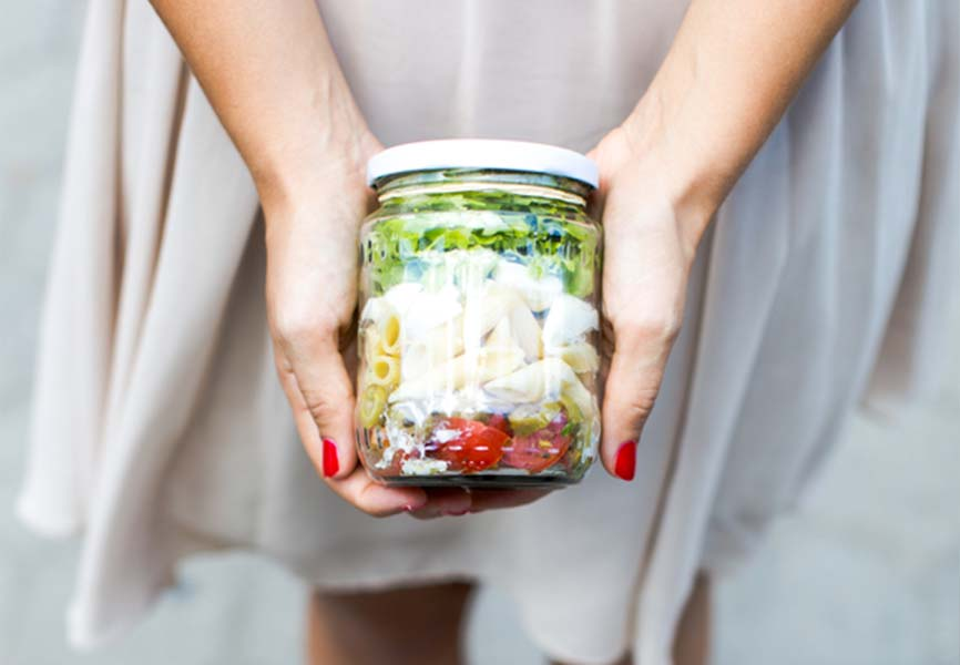Woman holding mason jar containing food