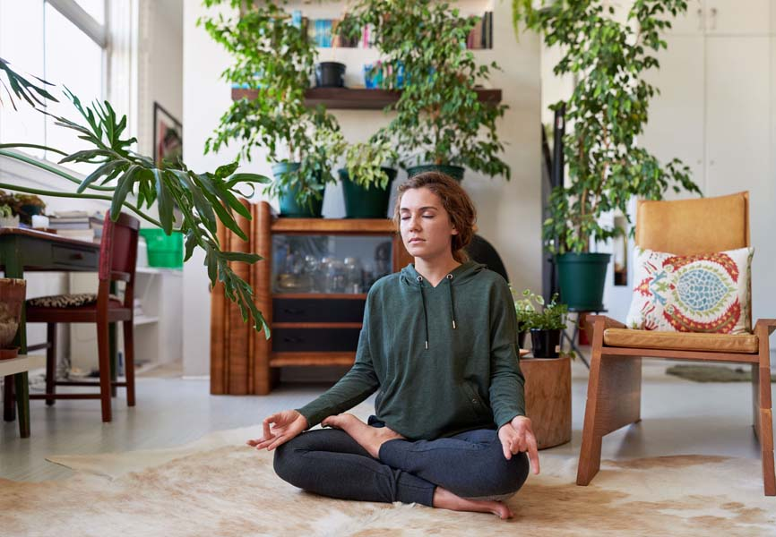girl meditating on living room floor with plants all around her