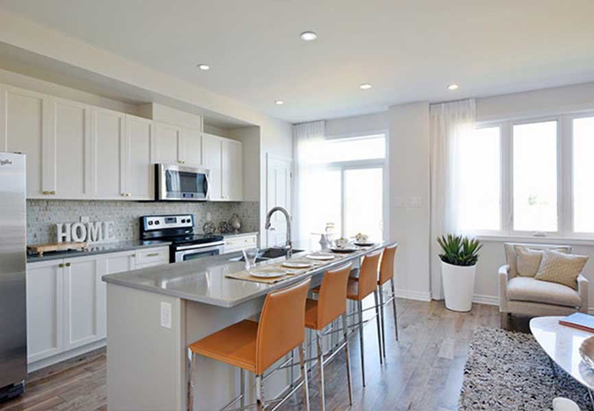 Light grey kitchen island with orange chairs