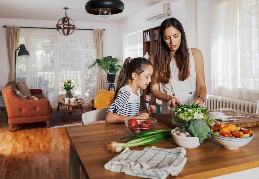 Mother and daughter cutting vegetables