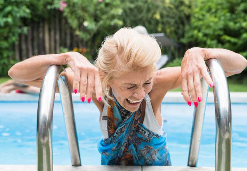 Older lady laughing on a pool ladder
