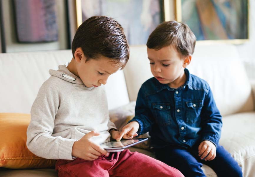 two little boys sitting on couch in living room looking at an iPad