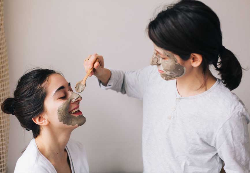 Woman applying a face mask to her friend